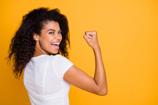 Photo of brunette haired cheerful cute nice curly wavy trendy youngster showing the power in her muscular arm shouting satisfied about her achievement isolated vivid color background in white t-shirt