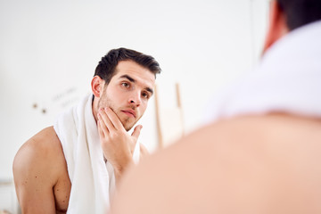 Unshaven brunet with white towel on his neck standing near mirror