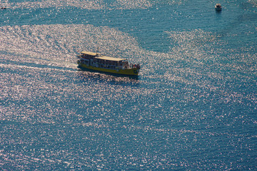 A tourist ship glides over the blue surface of the sea, covered with glare from the sun's rays
