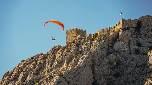 Paraglider flies past the walls of the medieval pirate fortress Stari Grad, Croatia