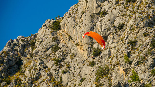 Paraglider flies along the steep stone slopes of the mountains, city Omis, Croatia