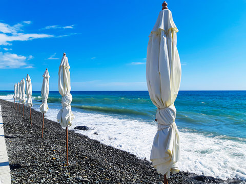 Eight white beach umbrella stands in a line along the shore next to the sea on which the wind made waves amid a bright sky