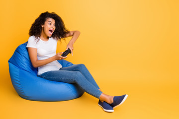 Portrait of nice attractive lovely cheerful cheery glad wavy-haired girl sitting in bag chair playing video game having fun isolated over bright vivid shine vibrant yellow color background