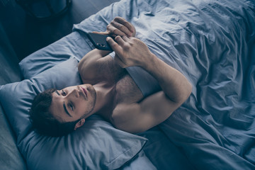High angle above view photo of handsome homey macho guy lying morning bed alone holding telephone sending message lover mistress calling home visit him sheets room indoors