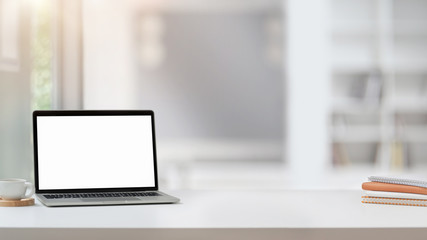 Close up view of workplace with blank screen laptop, copy space, notebooks and coffee cup on white...
