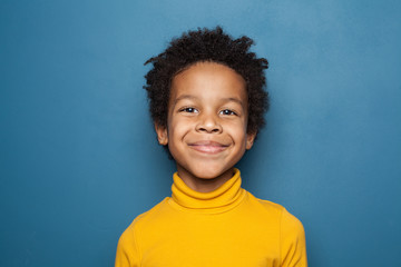 Happy child portrait. Little african american kid boy on blue background Fotomurales