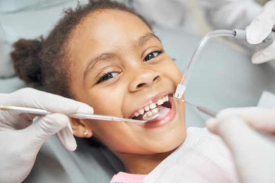 Cute african girl during dental treatment at modern clinic