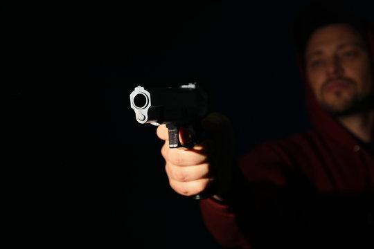 Man holding gun on dark background, focus on hand