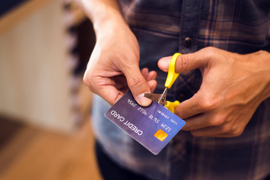 Hands cutting a credit card with scissors,copy space,vintage tone.