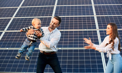 Happy young family with a little blond child having fun on the background of solar panels. A modern world with continuously advancing technology