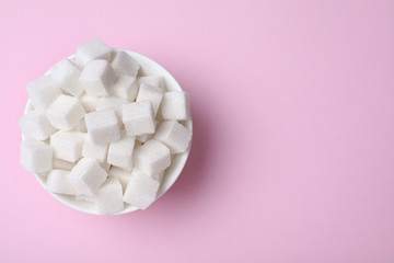Refined sugar cubes in bowl on pink background, top view. Space for text