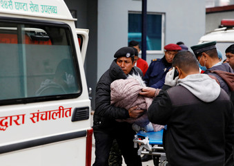 A body of a child who is among the eight Indian tourists who died due to suspected suffocation is being carried inside an ambulance while being taken for postmortem in Kathmandu