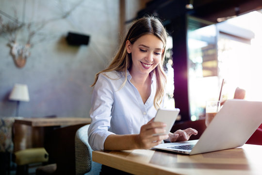 Portrait of cheerful coworker business woman working on laptop