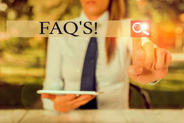 Text sign showing Faq S. Business photo showcasing list of questions and answers relating to particular subject Female business person sitting by table holding mobile phone