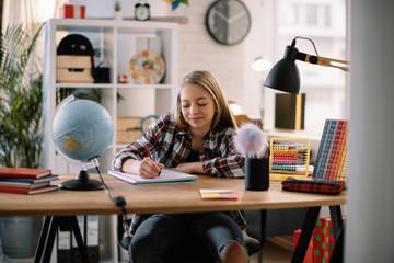 Beautiful girl learning at home. Schoolgirl doing homework.