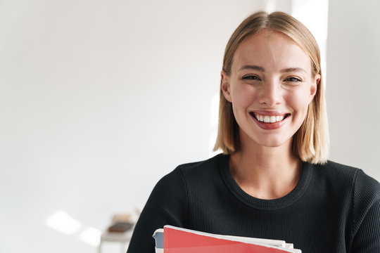 Blonde woman student indoors holding copybooks.