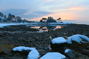 Fotobehang - The coast of the Atlantic Ocean at dawn. A beautiful stony shore and a magnificent sky above the sea. USA, Maine. Beautiful winter dawn.