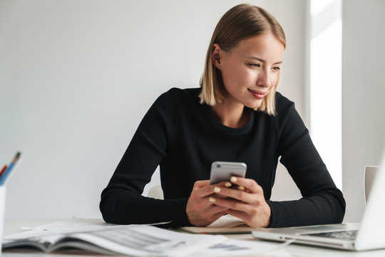 Blonde business woman work with documents and phone.