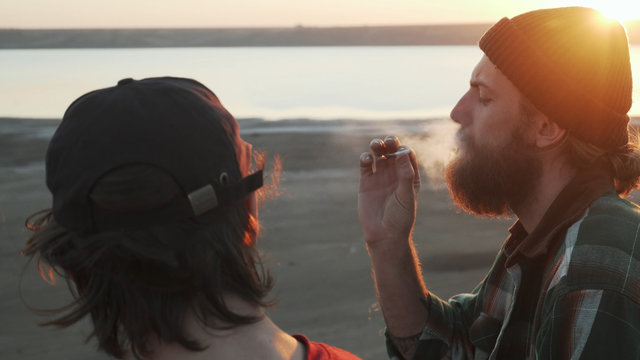 Two friends smoking joint with weed at seashore at sunset