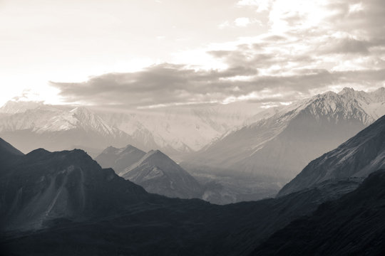 Nature aerial landscape view black and white photo of sunrise over snow capped Karakoram mountain range with morning fog in Nagar valley. Gilgit Baltistan, Pakistan.