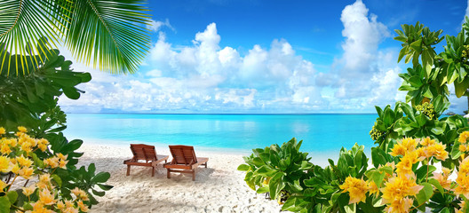 Beautiful tropical beach with white sand and two sun loungers on background of turquoise ocean and blue sky with clouds. Frame of palm leaves and flowers. Perfect landscape for relaxing vacation.