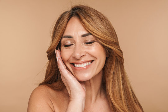 Portrait of shirtless adult woman touching her face and smiling