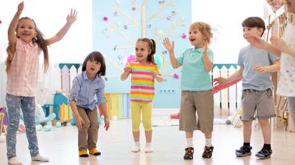 Cheerful kids stand semicircle on floor in kindergarten or daycare centre. Preschoolers have fun indoors, playing games