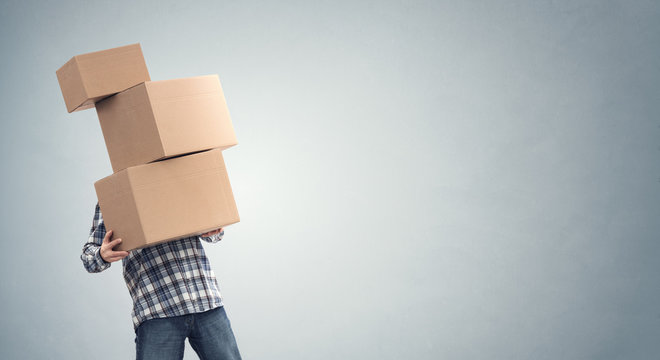Man holding heavy cardboard boxes relocation, moving house or courier delivery