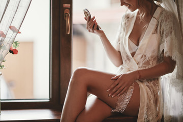 cropped photo of beautiful young bride on the window in her underwear and holds a mirror in his hands. bride's wedding morning preparation. Boudoir. Wedding.