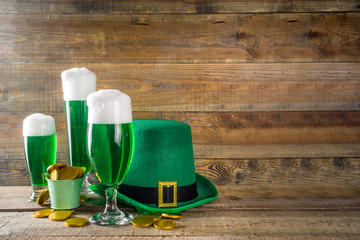 In de dag Alcohol Traditional irish alcohol for St Patrick's day party. Different glasses with green beer, with golden chocolate coins decor and green leprechaun hat. Old rustic wooden background copy space