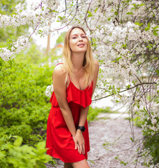 Portrait of a beautiful girl among spring foliage and flowers