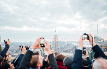 Tourists on a rooftop in New York City taking pictures with smartphon to the skyline