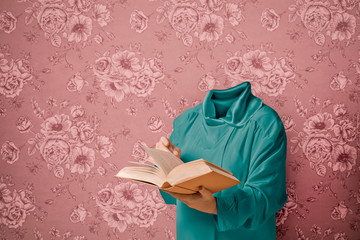 Woman with no head reading book while standing against wall