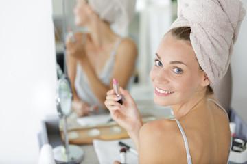 happy beautiful woman applies lip gloss