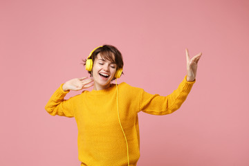 Funny young brunette woman girl in yellow sweater posing isolated on pastel pink wall background studio portait. People lifestyle concept. Mock up copy space. Listen music with headphones, dancing.