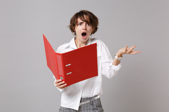 Shocked young business woman in white shirt posing isolated on grey background studio portrait. Achievement career wealth business concept. Mock up copy space. Holding red folder for papers document.
