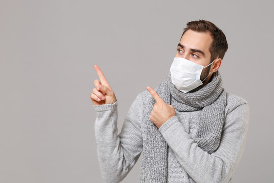 Young man in gray sweater, scarf isolated on grey background. Healthy lifestyle, ill disease treatment, cold season concept. Mock up copy space. Wearing sterile face mask point index fingers aside up.