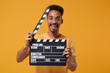 Laughing young african american guy in casual t-shirt posing isolated on yellow orange background in studio. People lifestyle concept. Mock up copy space. Hold classic black film making clapperboard.