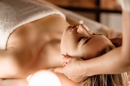 Hands of the masseuse make a manual massage of the head to a beautiful client woman. Concept of scalp treatment and hair growth stimulation