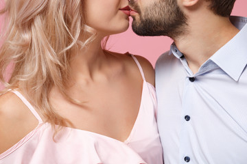 Cropped image of kissing young couple two guy girl in party outfit celebrating posing isolated on pastel pink wall background. People lifestyle Valentine's Day Women's Day birthday holiday concept.