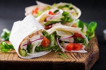 Fresh tortilla wraps with chicken and fresh vegetables on wooden board. Chicken burrito. Mexican food. Healthy food concept. Mexican cuisine.