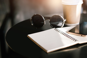 Close-up of mobile phone on blank notebook with sunglasses and coffee cup on desk
