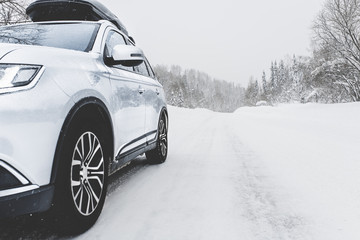 Suv car with rooftop cargo carrier trunk stay on roadside of winter mountain road in snowy blizzard. Family trip to ski resort. Winter holidays adventure. car on winter road