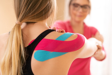 Young female patient wearing kinesio tape on her shoulder exercising with a professional physical therapist. Kinesiology, physical therapy, rehabilitation concept.