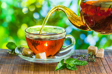 Foto op Plexiglas Thee Tea time. Pouring out hot tea into a cup. Green nature background.