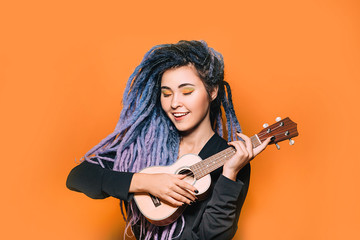 Rastafarian woman and dreadlocks and bright makeup plays on ukulele. Musical instrument ukulele