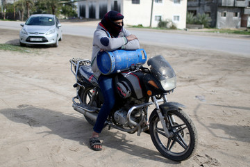 A Palestinian man on a motorcycle waits to fill a cylinder with cooking gas in Rafah in the southern Gaza Strip