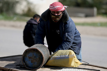 A Palestinian man waits to fill a cylinder with cooking gas in Rafah in the southern Gaza Strip