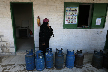 A Palestinian woman waits to fill cylinders with cooking gas in Rafah in the southern Gaza Strip