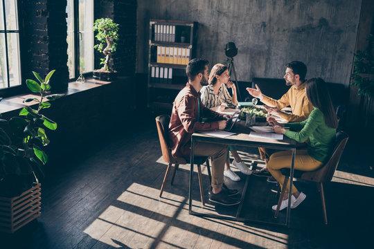 Focused serious professional freelancer sit table desk analyze start-up development innovation progress project talk say speak tell smart ideas in workplace dark sunny office